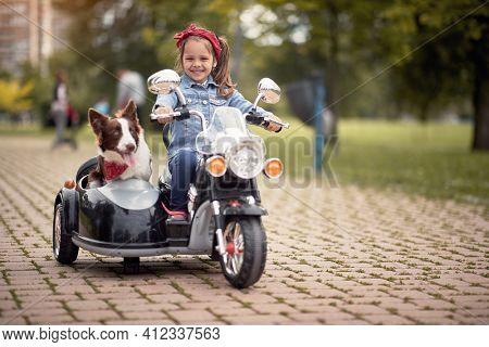 cute little girl  driving electrical motorcycle toy with sidecar and her dog in it. looking at camera, eye contact, smiling