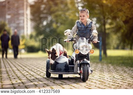 little boy standing on motorcycle toy with sidecar and dog in it