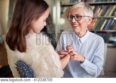 Grandma is full of love for her granddaughter while spending time in a relaxed atmosphere at home together. Family, leisure, together