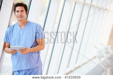 Doctor Using Digital Tablet In Corridor Of Modern Hospital