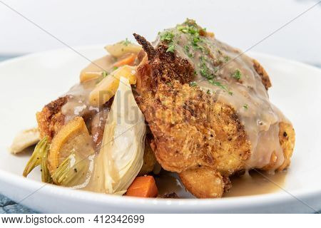 Braised Chicken Piled Onto A Plate Covered In Gravey Sitting On Top A Bed Of Vegetables.