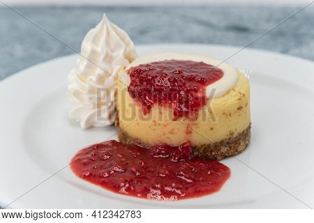 Tasty Treat For That Sweet Tooth With A New York Style Cheesecake Presented With Whipped Cream.