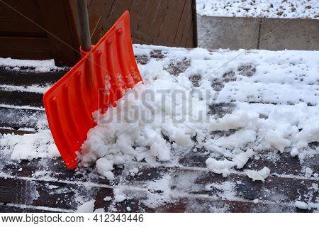 Shoveling Snow Slush On Wooden Porch With Orange Shovel And Clear Sidewalk