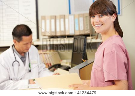 Nurse With Doctor Working At Nurses Station