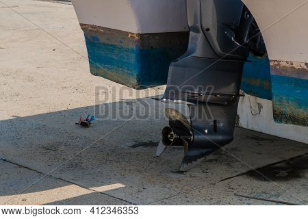 Closeup Of Black Propeller And Rudder Shaft Of Outboard Engine Used To Power Small Boat