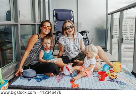 Young Mothers Spending Time Together With Children Babies On A Balcony At Home. Lgbtq Female Parents