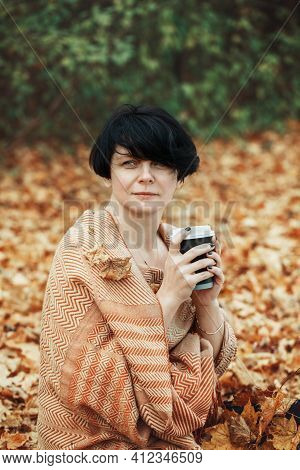 Middle Age Caucasian Brunette Woman With Short Bob Hair Wrapped In Woollen Scarf Outdoor. Woman Sitt