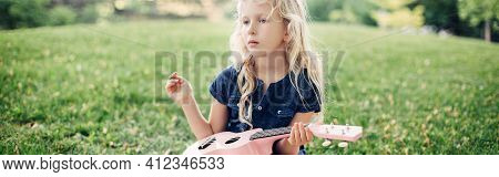 Girl Playing Pink Guitar Toy Outdoors. Child Playing Music And Singing Song In Park. Music Hobby Act
