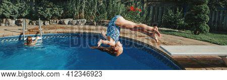 Brave Athletic Girl In Swimsuit Diving In Pool From Springboard. Child Kid Enjoying Having Fun In Sw
