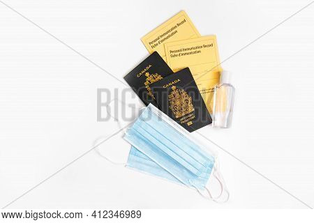 Two Canadian Passports With Yellow Immunity Vaccination Records, Face Sanitary Blue Masks And Saniti