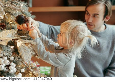 Happy Caucasian Father With Baby Girl Decorating Christmas Tree With Ornaments Baubles Toys. Happy F