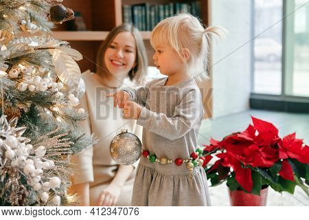 Happy Caucasian Mother With Baby Girl Decorating Christmas Tree With Ornaments Baubles Toys. Happy F