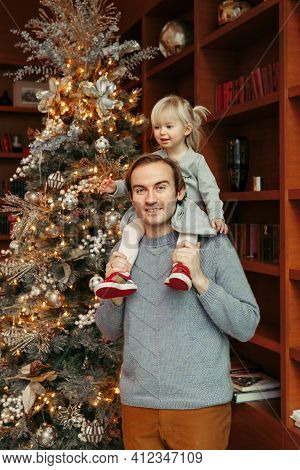 Smiling Caucasian Father Holding Baby Girl On Shoulders By Decorated Christmas Tree. Happy Family Ce