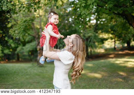 Happy Childhood. Young Smiling Caucasian Mother And Girl Toddler Daughter Playing In Park. Mom Tossi