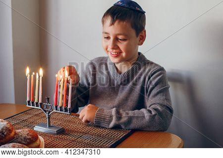 Boy In Kippah Lighting Candles On A Menorah For Traditional Winter Jewish Hanukkah Holiday. Child Ce