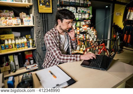 Small Business Owner On Phone And Computer In Store. Sport Shop Worker Making Call With Cell Phone.