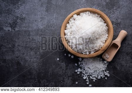 Salt In Wooden Bowl On Stone Table. Salt Top View. Sea Salt On Dark Background.