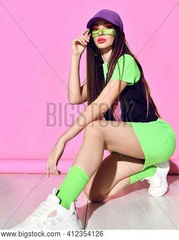 Stylish Daring Impudent Young Woman With Colored Hair Wearing Short Dress, Cap, Vest And Sneakers Si
