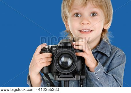 Portrait Of Cute Little Smiling Boy With Camera On Tripod