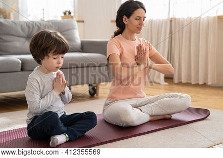 Mommy Practicing, Teaching Child To Meditate. Fit Mom With Little Son Doing Yoga Exercise Sit On Yog