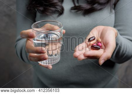 Close Up Of Woman Holding Pill And Glass Of Water,diet Concept.capsules Vitamin And Dietary Suppleme