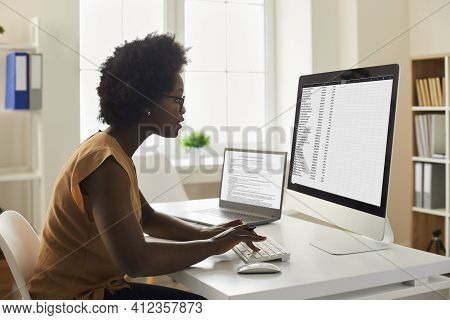Young African-american Woman Sitting At Office Desk And Working With Data On Computer