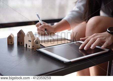 Wooden Toy House With Woman Plan To Sign A Contract To Buy A House, Real Estate Concept.
