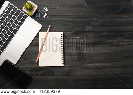 Modern Dark Wood Office Desk Table With Laptop, Smartphone And Other Supplies. Blank Notebook Page F