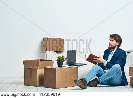 A Man Sits On The Floor Of A Box With Things Office Moving Unpacking Official
