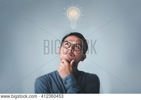 Thinking Asian Man In Glasses Looking Up With Light Idea Bulb Above Head On Gray Background.creative