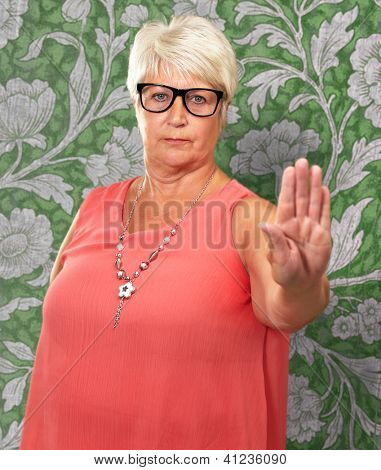 Portrait Of A Senior Woman Showing Stop Sign On Wall Paper