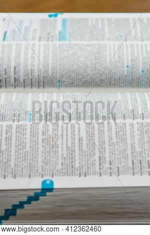 Unfocused Pages Of Open Dictionary On Brown Background.