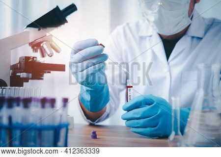 Researcher With A Tube Of Biological Sample Contaminated By Coronavirus With Label Coronavirus, Doct