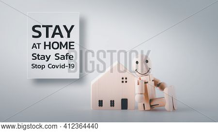 Wooden Doll Stands Next To The House And Has Sign Showing Stay At Home Stay Safe Stop Covid-19. Soci