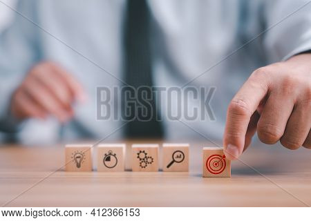Business Development Strategy And Action Plan Concept. Hand Arranging Wood Block With Icon Business