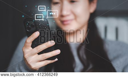 Asian Women Using Smartphone Typing, Chatting Conversation Working Home In Chat Box Icons Pop Up. So