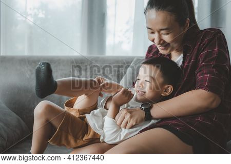 Asian Beautiful Mother And Child Happily Hugged And Kissed Each Other's Cheeks. Asian Family Mom And