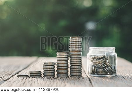 Saving Money And Investment Concept. Money Coin Stack Growing Graph And Coins In Jug Glass. Balance