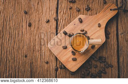 Espresso Coffee In Cup And Coffee Beans On Old Wood Table. Espresso Shot.