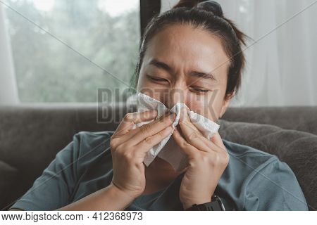 Sick Asian Woman Sitting Indoors Holding Tissue Handkerchief Blowing Running Nose Feels Unwell Unhea