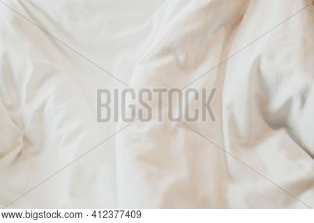 Top View Of White Duvet On The Bed With Sunlight. Bedroom With White Bed.