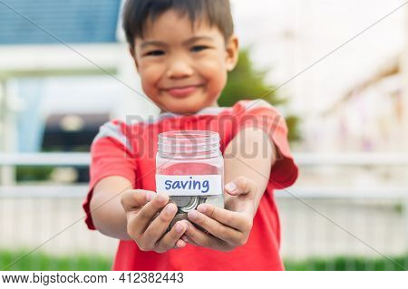 Portrait Of Happy Asian Child Boy Holding The Jar Of Coins. Childhood Showing The Coins. Kid Saving
