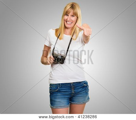 Happy Woman With Old Camera Showing Thumb Up against a grey background