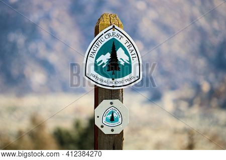 March 13, 2021 In Snow Creek, Ca:  Pacific Crest Trail Sign Post On An Arid Field With Barren Mounta