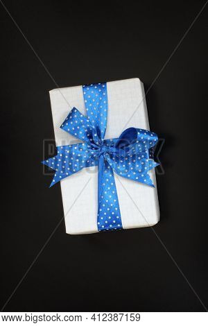 Gift With A Blue Ribbon With Polka Dots On A Dark Background Top View. Surprise For The Holiday