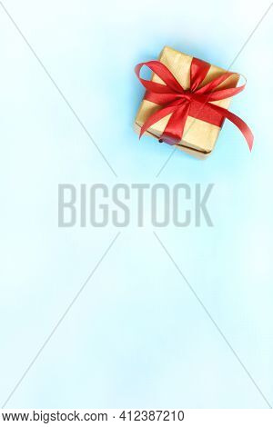 Box Wrapped In Kraft Paper With A Red Ribbon And Bow On A White And Blue Background. Gift For Any Ho
