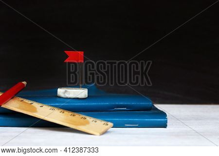 Blue Notebook And Eraser Wash With A Red Flag On The Background Of The School Blackboard. Towards Th
