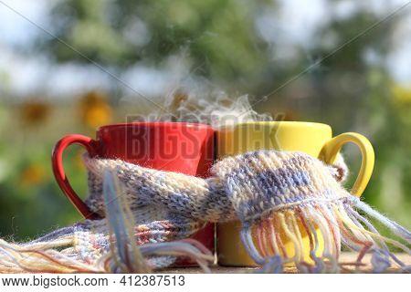 Red And Yellow Mugs Wrapped In A Scarf On A Garden Background In The Afternoon. Joint Warming Breakf
