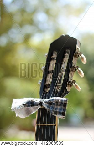 Guitar Neck Decorated With Bow Tie On The Background Of Blurred Greenery Of The Park. Stylish Street