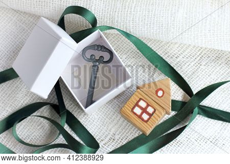 Box With A Key Inside And A Small Wooden House Next To The Table Top View. Open Holiday Gift